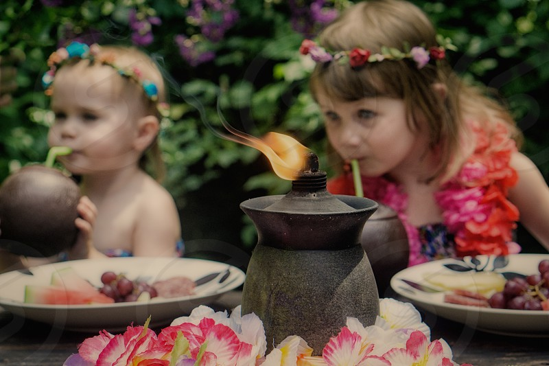 toddler girls wearing leis on a picnic sip from coconuts by candlelight  photo