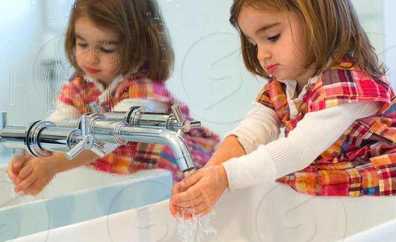 girl in pink orange white checkered vest washing her hands in white ceramic sink beside wall mirror photo