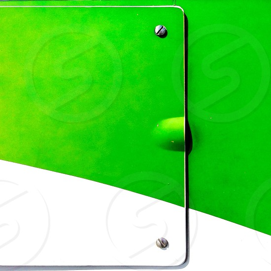 white and green metal sheet with 2 screws photo