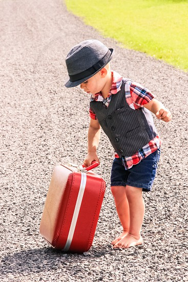 Little boy child toddler red suitcase blue jean shorts vest plaid shirt hat fedora bare feet toes country rural dirt gravel road drag haul lift carry tote outside outdoors grass summer prodigal moving vacation travel traveler stranded hobo nomad drifter independent independence adventure photo