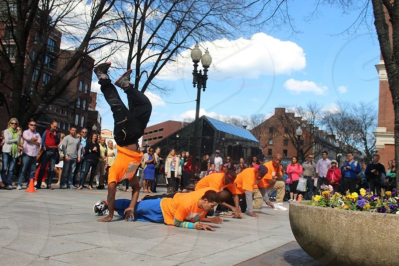 men in orange t shirts doing breakdancing in plaza with crowd photo