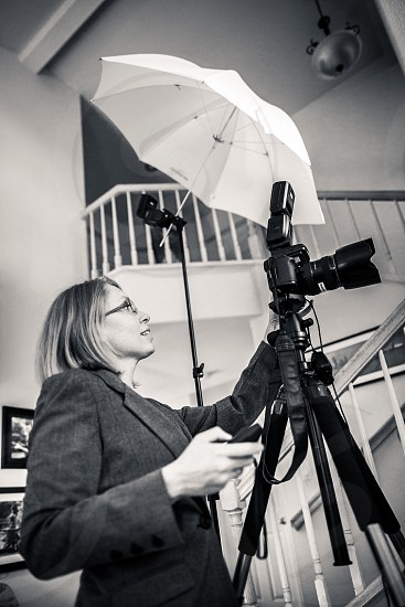 A professional photographer shoots a property. House stairs grey blazer yellow woman lady female girl tripod camera flash remote architecture structure building real estate home off-camera-flash umbrella trigger. Black and White. photo