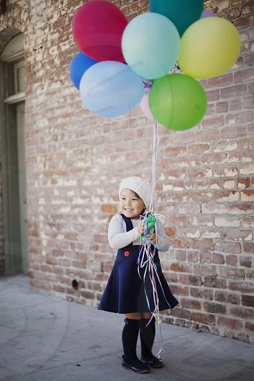 girl wearing white bonnet white long sleeved shirt and blue blouse holding 7 balloons photo