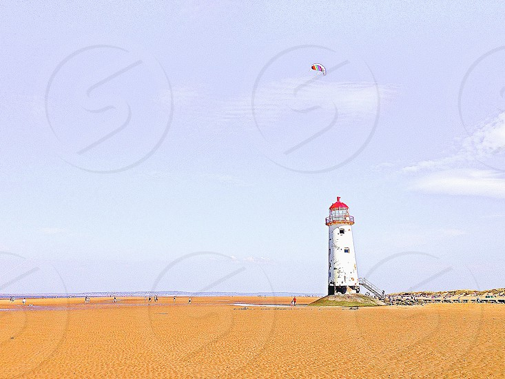 panorama exposure of white and red lighthouse on brown sand under blue sky during daytime photo