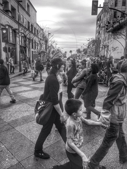 gray scale photo if people walking on marble flooring outdoor near establishments photo