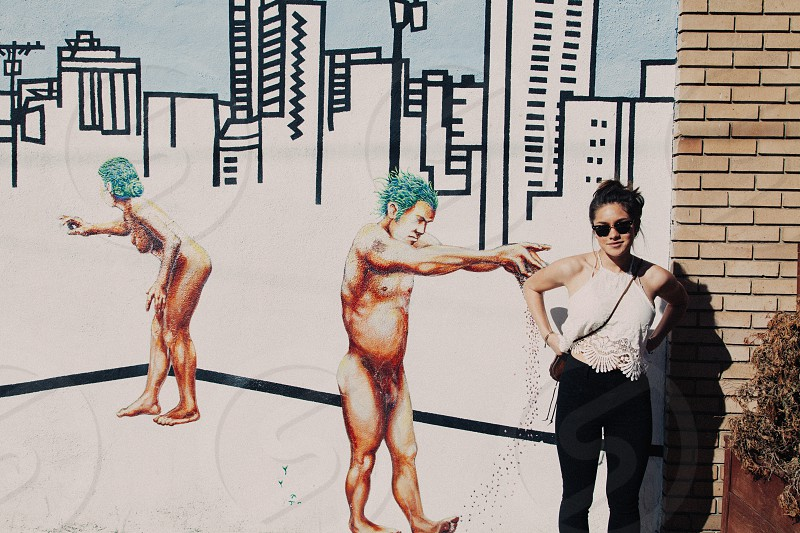 topless people painting beside woman in white halter top and black leggings wearing sunglasses during daytime photo