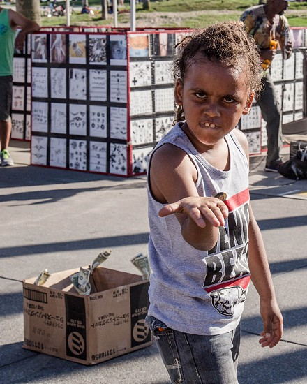 Young African-American boy begging for money.  Street Performer.  Street Photography. Urban photography. photo