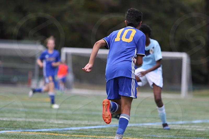Teenage boy playing soccer running downfield photo
