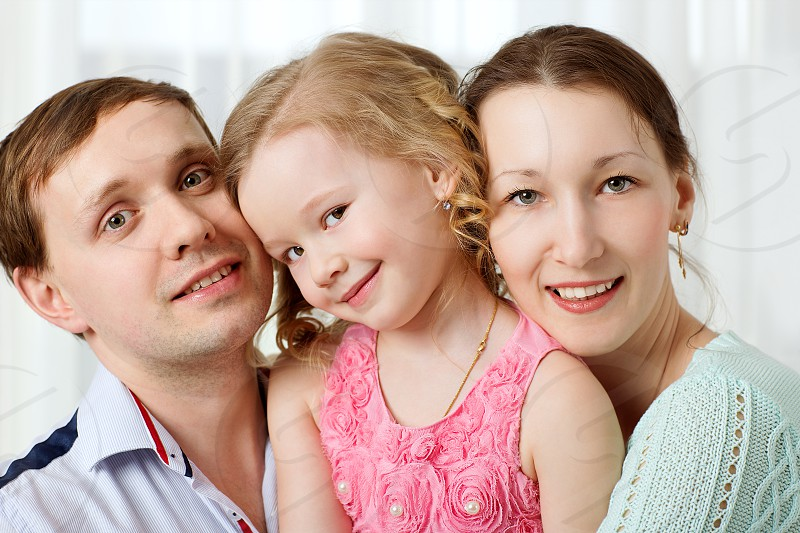 Portrait of happy family. Young parents with cute little daughter. Girl looking shy photo
