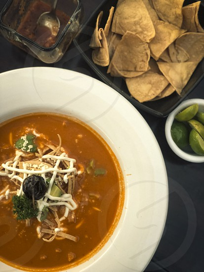 Traditional Mexican dish - a tortilla soup serving with lime tortilla chips and salsa photo
