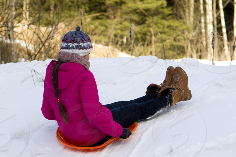 The girl intends to move down a hill on ice-boats in a snowy winter forest. photo