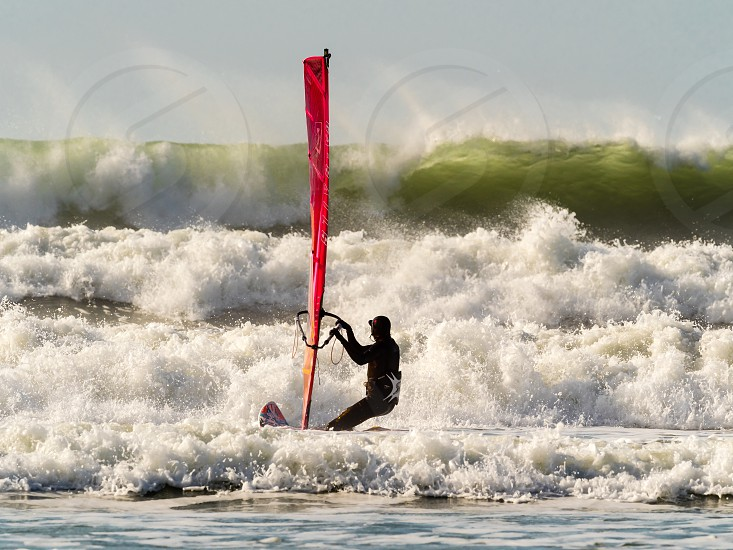 The Windsurfer and the High Wave. A windsurfer at Newgale in Pembrokeshire anticipating the high wave. photo