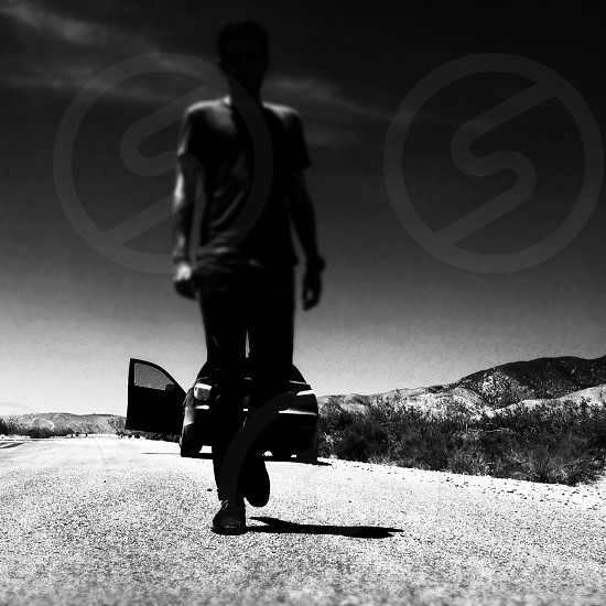 grayscale photo of a man walking in road photo