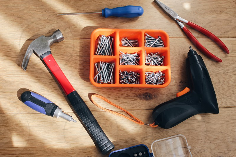 black red and silver curved claw hammer blue screwdriver and red needlenose pliers near nails on orange plastic container photo