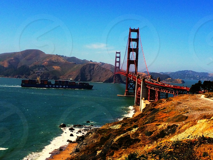 red gated bridge over body of water and mountainous landscape photo