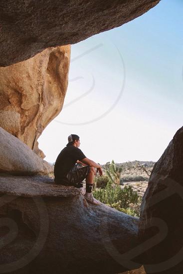man in black shirt sitting on rock photo