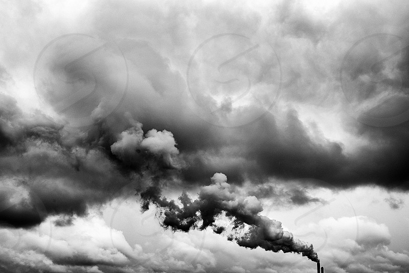 Black and white image showing the chimneys of a factory releasing pollution into the air merging into thte clouds photo