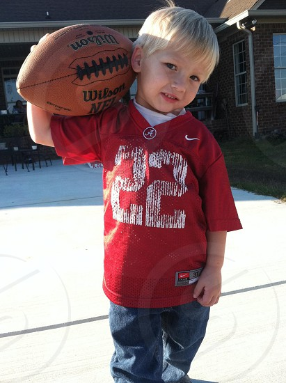 toddler wearing red 22 jersey and blue pants carrying basketball photo