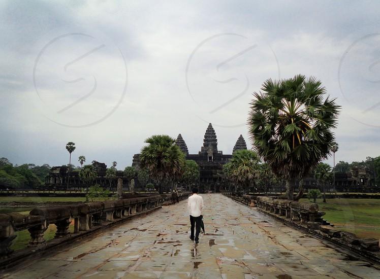 man in white shirt walking on pathway photo