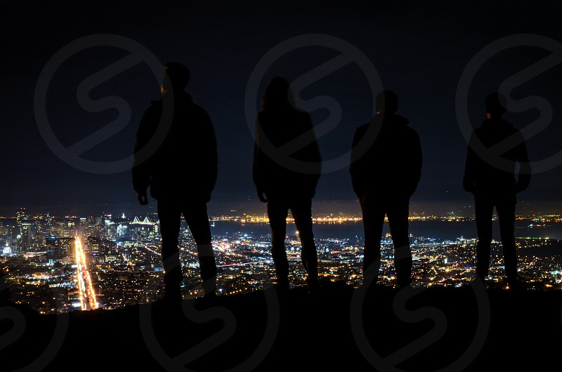 four people standing silhouettes on a hill overlooking city lights in a valley photo