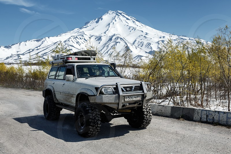 KAMCHATKA PENINSULA RUSSIAN FAR EAST - JUNE 18 2017: Four-wheel drive japanese car - SUV Nissan Safari rides on country mountain road against background of snow-capped cone of Vilyuchinsky Volcano photo