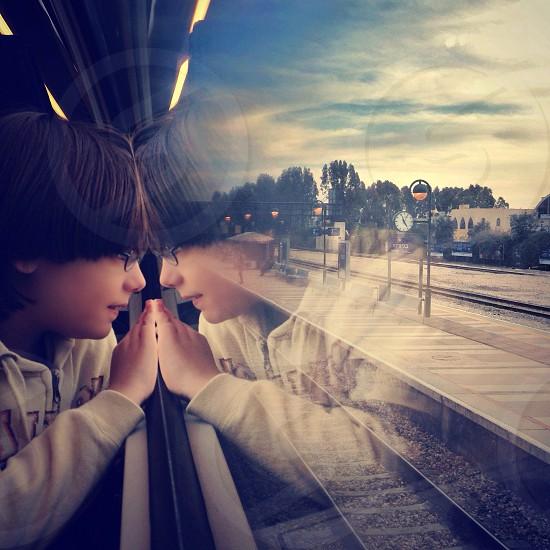 boy wearing white zip jacket inside the train looking outside from glass window photo