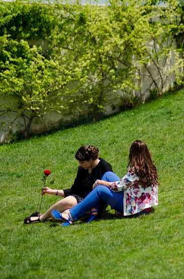 woman holding red rose sitting besides woman photo