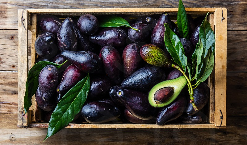 Box of fresh avocado with leaves on wooden background. Harvest concept photo