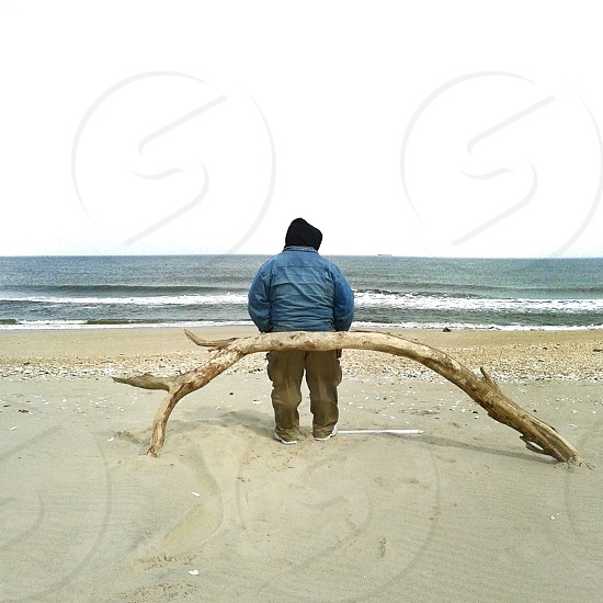 person in blue jacket standing on white sand beach photo