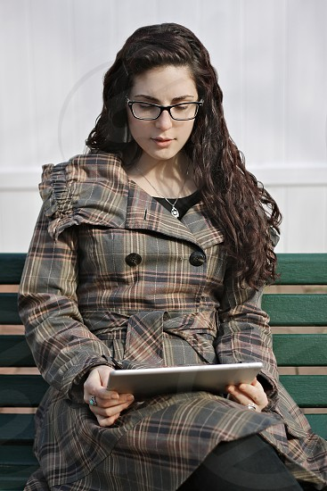 Young woman on a park bench using a tablet photo