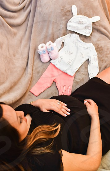 Pregnant woman sitting on a couch with baby clothes laying before her.  photo