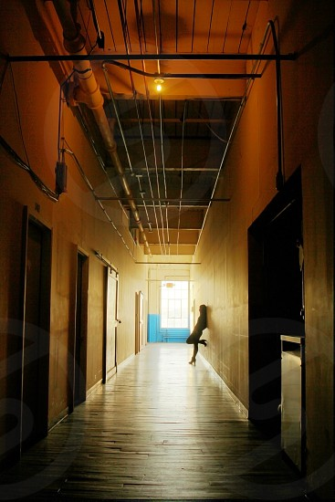 woman leaning against hallway wall photo