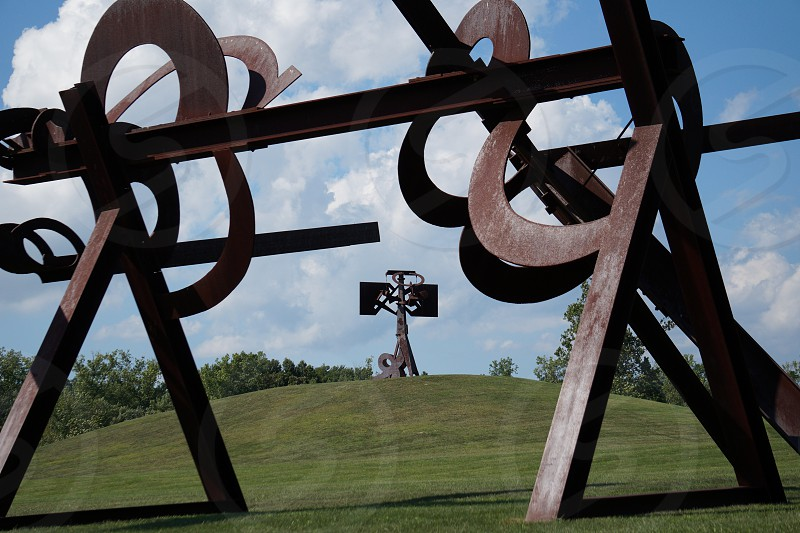brown metal bar on grassy hill with trees photo