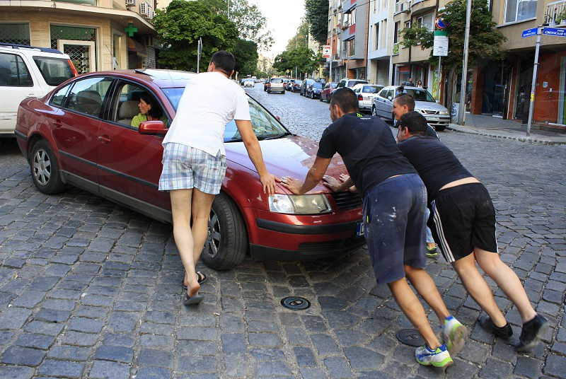 Men helping a woman with the car photo