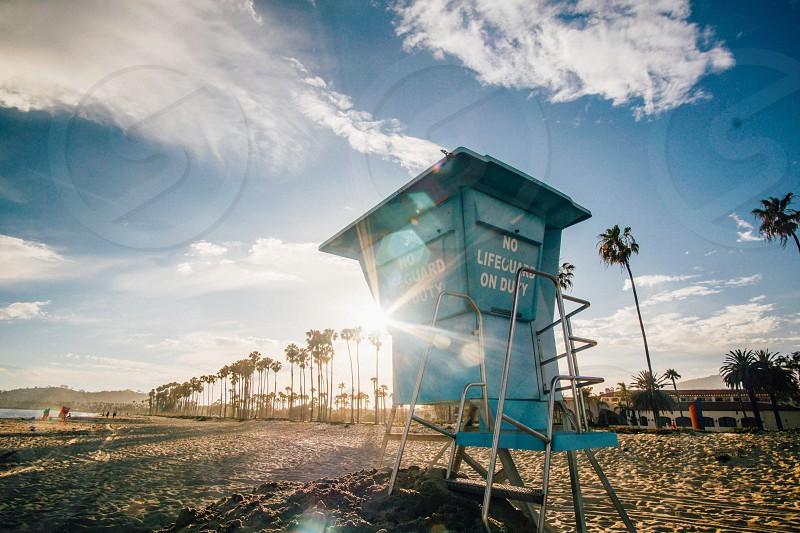 lifeguard beach duty tower palm tree sun glare flare sky clouds sand ocean california santa barbara photo