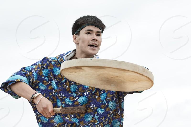 KAMCHATKA PENINSULA RUSSIA - AUGUST 9 2014: Emotional man dancer dancing with a tambourine. Public concert Koryak Folk Dance Ensemble Angt on the Khalaktyrsky Beach around the Petropavlovsk-Kamchatsky City. photo