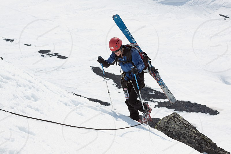AVACHINSKY VOLCANO KAMCHATKA PENINSULA RUSSIA - APRIL 21 2012: Open Cup of Russia on Ski Mountaineering on Kamchatka - ski mountaineer climbing on rope on rock with skis strapped to backpack. photo