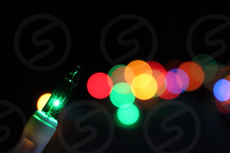 green light bulb with bokeh effects at the background photo
