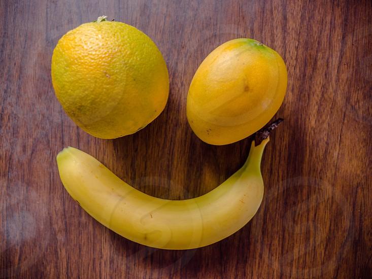 Fruit smiley concept from yellow banana orange and mango photo
