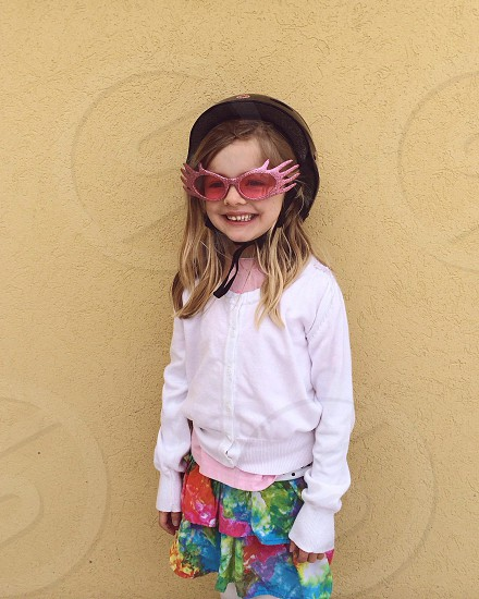 girl on white jacket and red sunglasses standing on brown wall photo