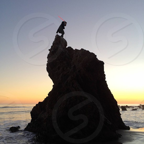 man with red sword standing on top of rock formation photo