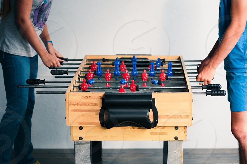 Young teenager boy playing table football with another player. Young people having fun spending time together photo