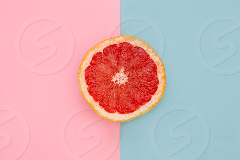 Pink grapefruit overhead on bright pink and blue background photo