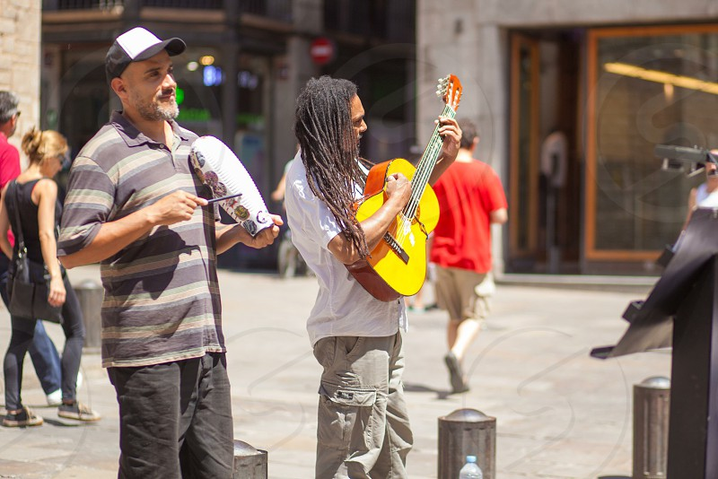 street performers using a yellow acoustic guitar photo