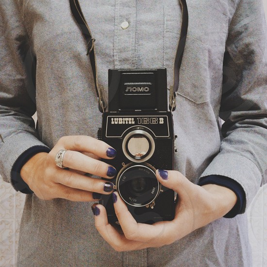 Hands adjusting the focus on a twin lens reflex camera. photo