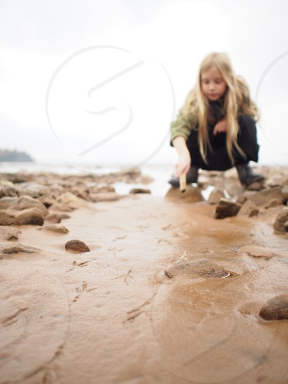 blonde long hair girl bending down on water and rocks flowing towards a beach photo