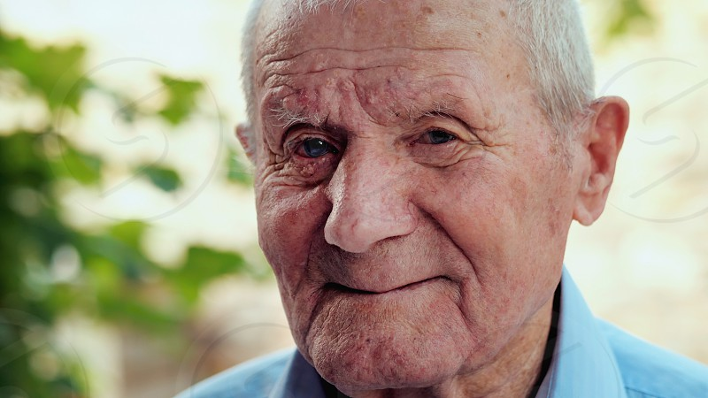 Very old man portrait with emotions. Grandfather is smiling and looking to camera. Portrait: aged elderly senior. Close-up of old man sitting alone outdoors. photo