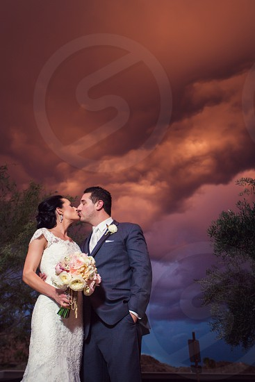Couple on their wedding day at sunset as storm clouds roll in. photo