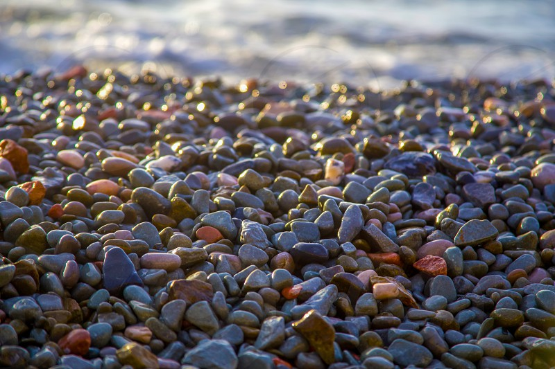 Abstract background with wet sea pebbles lit by the rising sun on the beach. photo