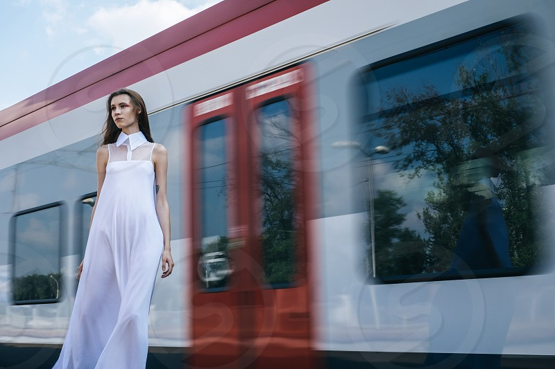 woman wearing white sleeveless collared illusion neckline maxi dress near red and grey train during daytime photo